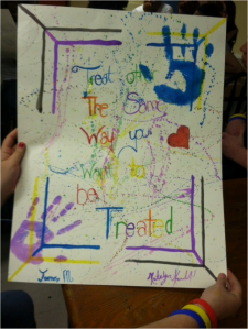 "This group chose ""This is what Leadership looks like"" for their topic and chose to paint a quote – ""Treat others the same way you want to be treated."" Their medium of choice was watercolor – they even painted their hands and stamped them on the paper!"