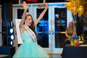 Friend of the Learning Center and Miss Teen Missouri USA Christina Stratten joins in on the live auction fun.